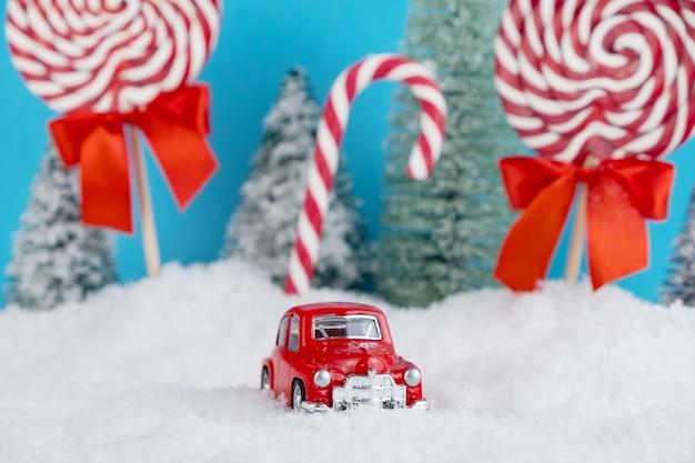 Automobile rossa della santa con nella foresta dell'albero di natale con caramelle e dolci lecca-lecca