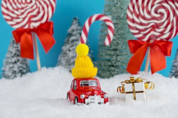 Automobile rossa della santa con scatole regalo e albero di natale nella foresta con caramelle e lecca-lecca