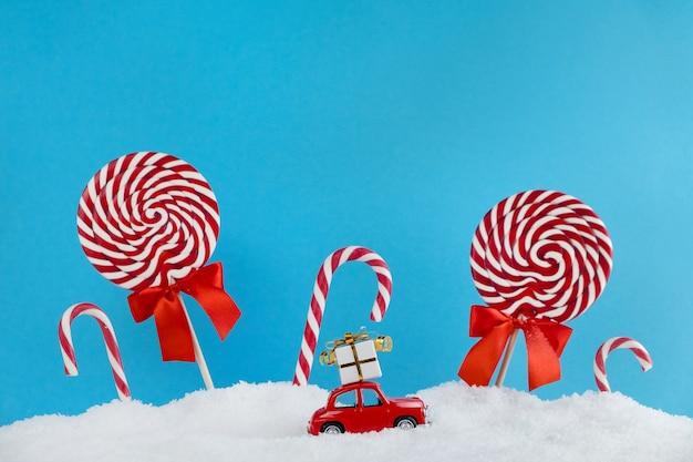 Automobile rossa della santa con il regalo sul tetto nella foresta dell'albero di natale con caramelle e dolci lecca-lecca