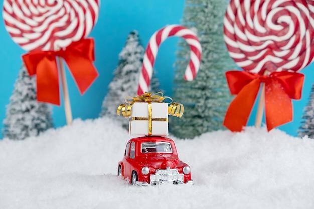 Automobile rossa della santa con il regalo sul tetto nella foresta dell'albero di natale con caramelle e lecca-lecca