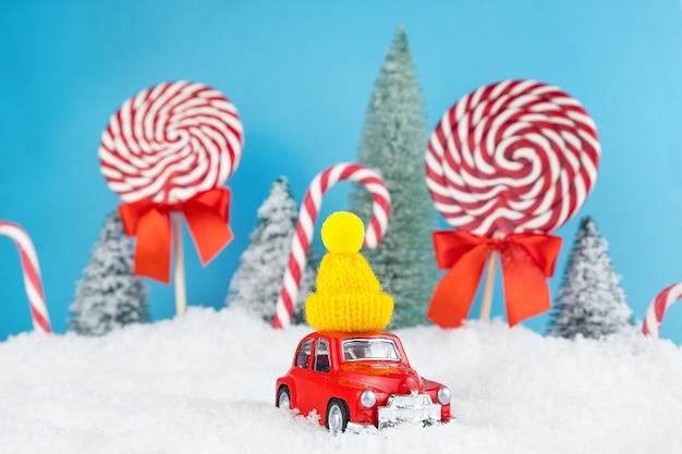 Automobile rossa della santa con il berretto invernale giallo e la foresta dell'albero di natale con caramelle e lecca-lecca