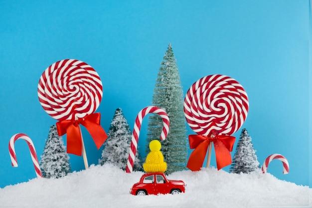 Automobile rossa della santa con in berretto invernale giallo e foresta dell'albero di natale