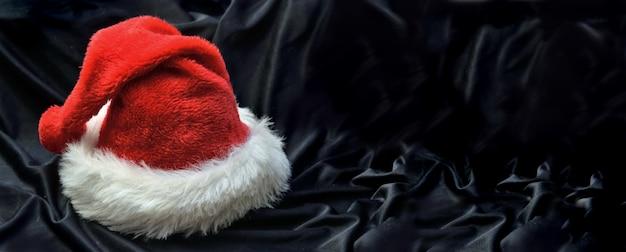 Cappello di babbo natale rosso in sfondo nero tessile