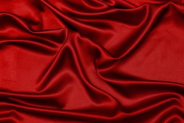 Raso rosso, tessuto setoso, onda, tendaggi. bellissimo sfondo tessile.