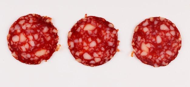 Salsiccia rossa affettata su una superficie bianca