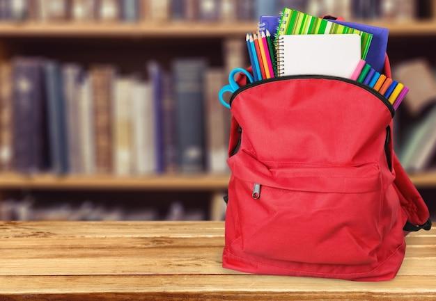 Zaino scuola rosso su sfondo.
