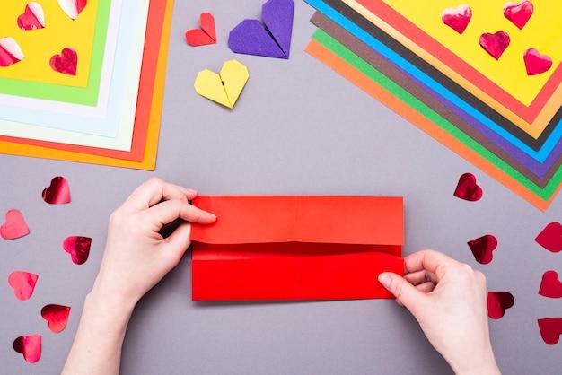 Foglio di carta rosso per il fatto a mano. creare un cuore segnalibro da un foglio di carta rossa
