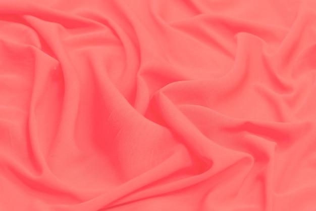 Struttura del tessuto di lusso in seta o raso rosso come sfondo astratto per il design. modello di vista dall'alto.