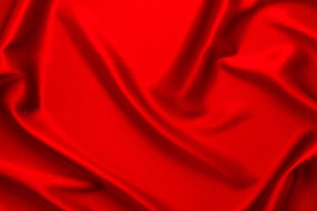 La trama del tessuto di lusso in seta rossa o satinata può essere utilizzata come sfondo astratto. vista dall'alto