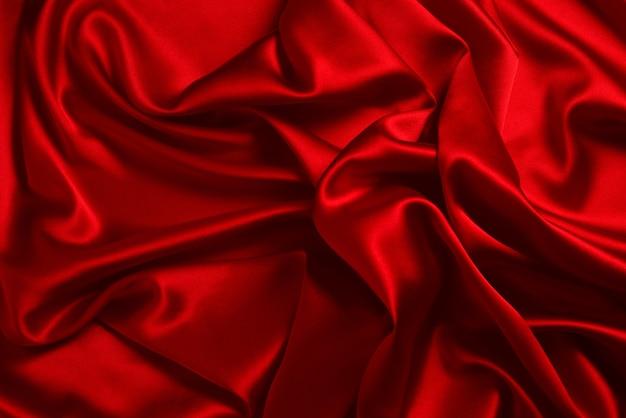La trama del tessuto di lusso in seta o raso rosso può essere utilizzata come sfondo astratto