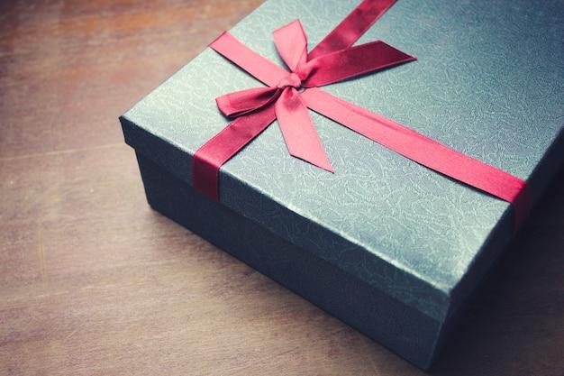 Piccola confezione regalo rossa su tavola di legno