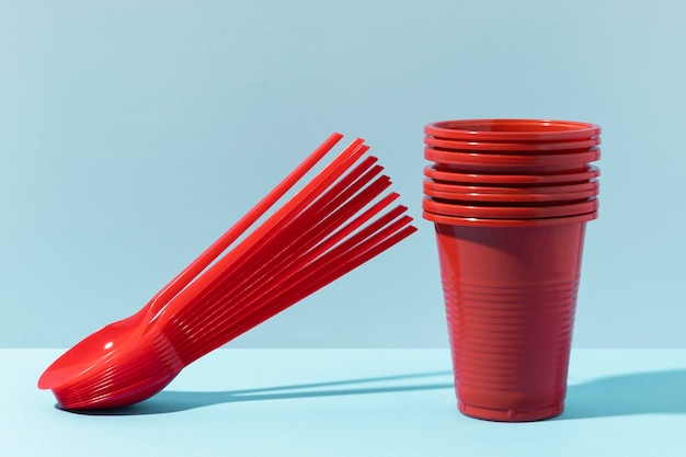 Vista frontale di piccoli cucchiai e bicchieri di plastica rossi