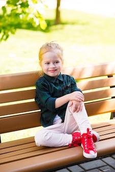 Scarpe da ginnastica rosse belle gambe sottili della ragazza con scarpe rosse e gonna di jeans