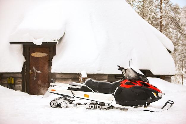 La motoslitta rossa è in piedi su una neve sullo sfondo di una capanna e di una foresta di tronchi di una casa invernale