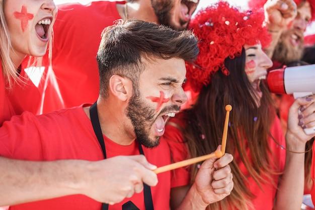 Appassionati di sport rossi che gridano mentre supportano la loro squadra fuori dallo stadio - i tifosi si divertono all'evento della competizione - campioni e concetto vincente - focus sul volto di uomo