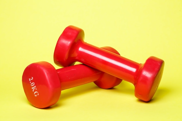 Manubri sportivi rossi su sfondo giallo