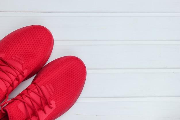 Scarpe sportive rosse per correre sul pavimento di legno bianco.
