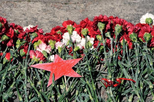 Stella rossa e fiori sul monumento dedicato alle vittime della ii guerra mondiale-victory day-may 9 a san pietroburgo, russia