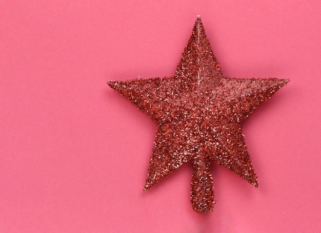Stella rossa posta su uno sfondo rosso e copia spazio per natale e capodanno