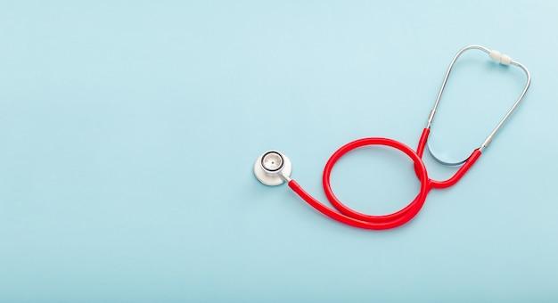 Stetoscopio rosso sul concetto di sfondo di colore blu di medicina e assistenza sanitaria pneumologia cardiologia vista dall'alto copia spazio per banner web lungo di testo