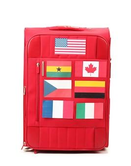 Valigia rossa con molti adesivi con bandiere di diversi paesi su bianco