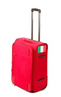Valigia rossa con adesivo con bandiera dell'italia isolato su bianco
