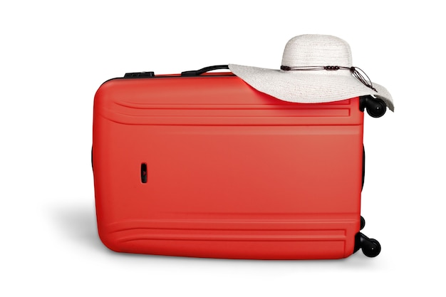 Valigia rossa con cappello per il sole nella vista frontale dall'alto