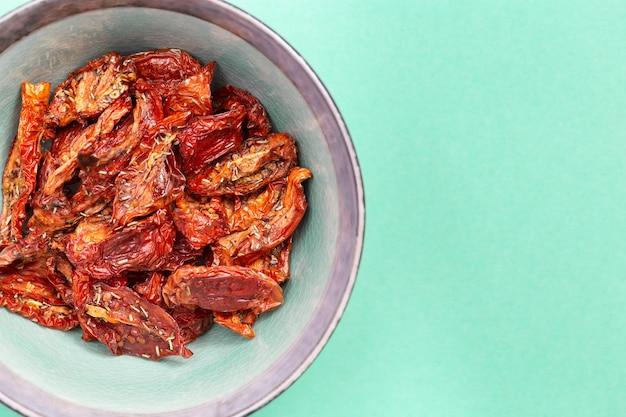 Pomodori secchi rossi nel piatto di ceramica su colorato