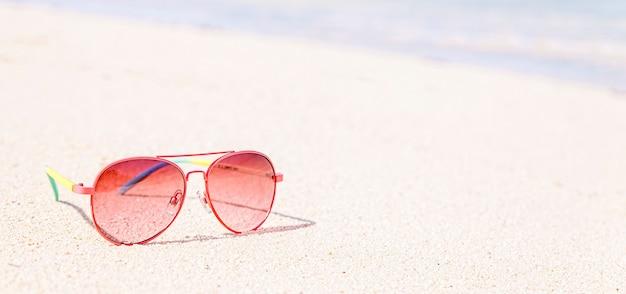 Occhiali da sole rossi sulla spiaggia, concetto tropicale, banner