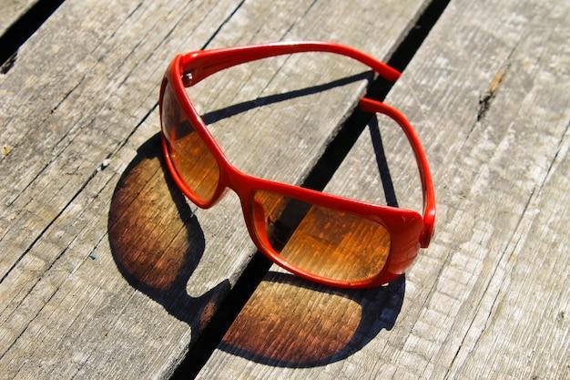 Occhiali da sole rossi sullo sfondo di legno