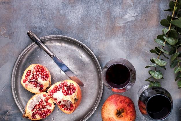 Bacche rosse dolci su un piatto di metallo vintage e coltello, due bicchieri di vino rosso