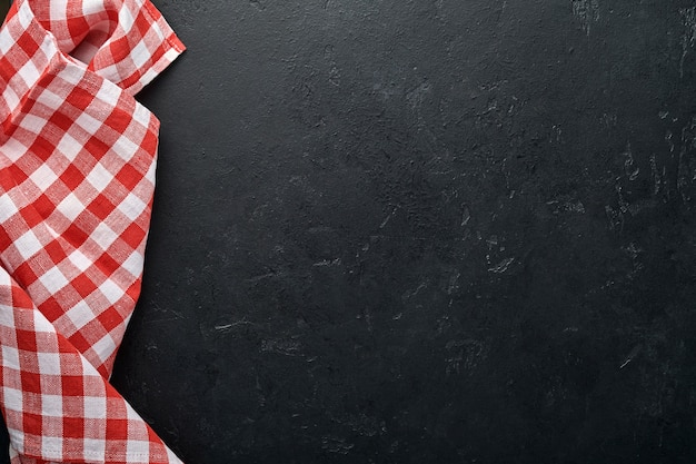 Tovaglia rossa sul colore nero del tavolo da cucina con per la tua ricetta o menu.