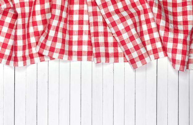 Tovaglia rossa sulla tavola di legno bianca, vista dall'alto