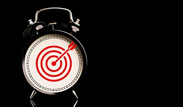 Tabellone rosso con freccia all'interno della sveglia su sfondo nero e copia spazio, tempo e concetto di obiettivo aziendale.
