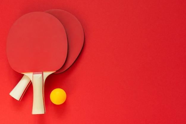 Racchette da ping pong da tennis rosse e palla arancione isolate su uno sfondo rosso, attrezzature sportive per il ping pong