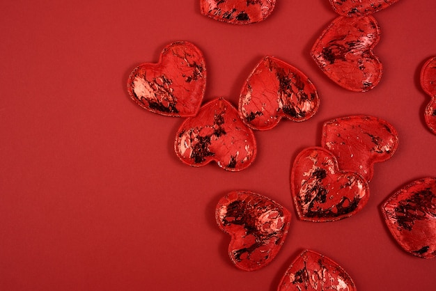 Piccoli cuori tessili rossi su sfondo rosso, sfondo festivo, vista dall'alto