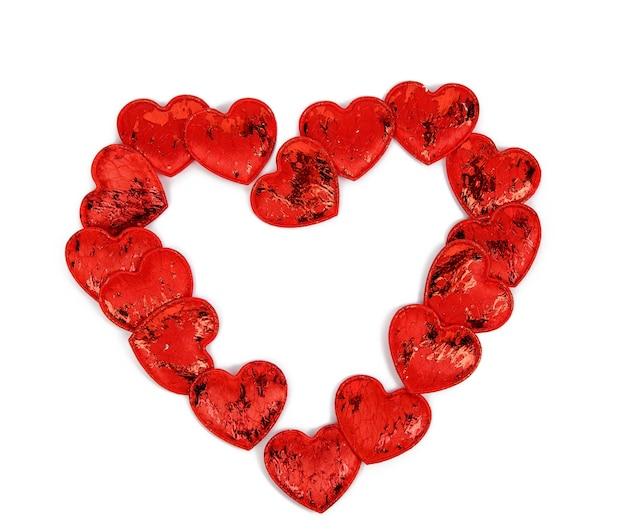 Piccoli cuori tessili rossi su sfondo bianco, sfondo festivo, forma di cuore