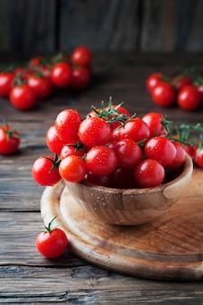 Pomodori rossi ciliegia sulla tavola di legno
