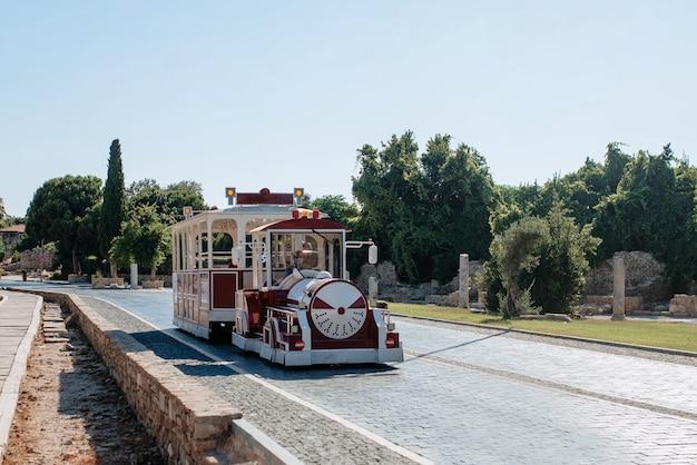 Un tram turistico rosso corre lungo la strada acciottolata della città di side in turchia. discernimento per i vacanzieri e trasporto dei turisti nei luoghi d'interesse della città.