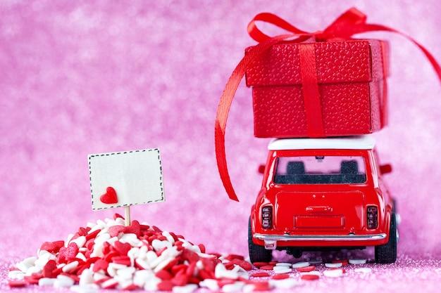 Automobile rossa del giocattolo che trasporta la confezione regalo sul tetto e la scheda vuota sul muro rosa lucido per il concetto di san valentino.