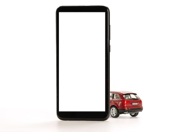 Auto giocattolo rossa e smartphone isolati su bianco, concetto di app online per car sharing, taxi, acquisto o vendita
