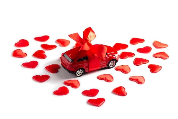 L'automobile rossa del giocattolo legata con un nastro sta nei cuori su bianco. concetto di san valentino