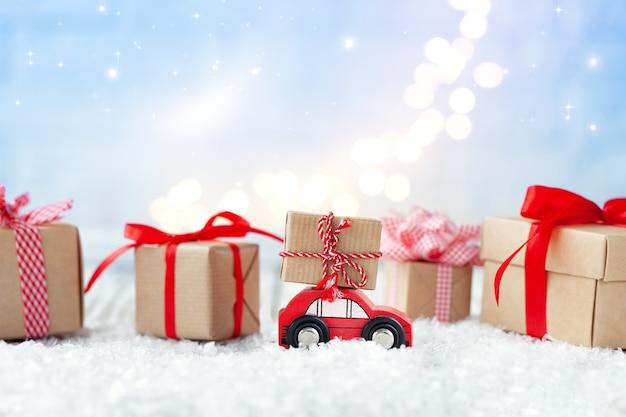 Macchinina rossa con un regalo sul tetto tra le scatole regalo di natale su sfondo blu con boke. biglietto di auguri festivo.