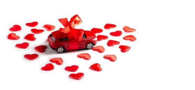 Automobile rossa del giocattolo con il nastro sta nei cuori su bianco. concetto di san valentino