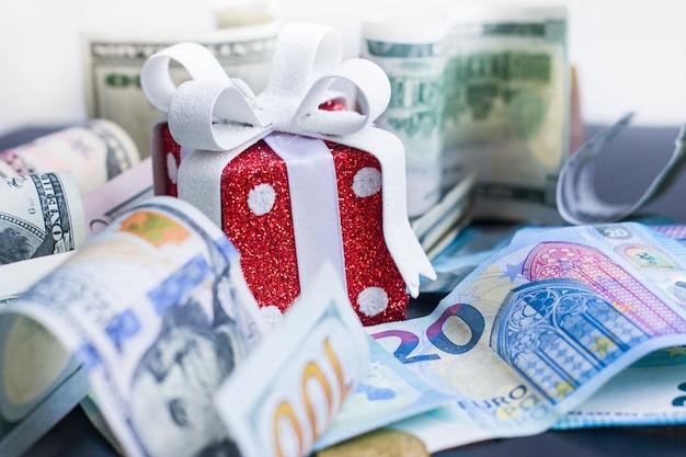 Regalo, dollari ed euro rossi del giocattolo sul nero