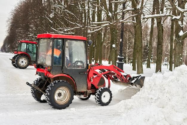 Il trattore rosso con un grande secchio rimuove la neve in un parco cittadino