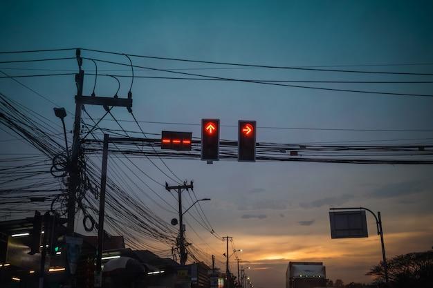 Semaforo rosso con fili disordinati su strada
