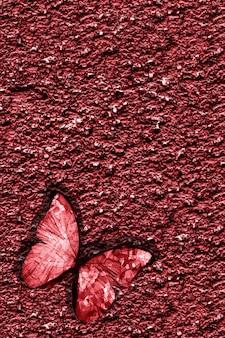 La farfalla tropicale rossa si siede sulla parete rocciosa rossa. foto di alta qualità