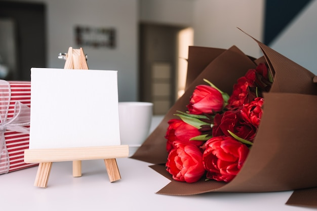 Bouquet di tulipani rossi con tazza di caffè. cornice bianca vuota. confezione regalo rosa. concetto di biglietto di auguri
