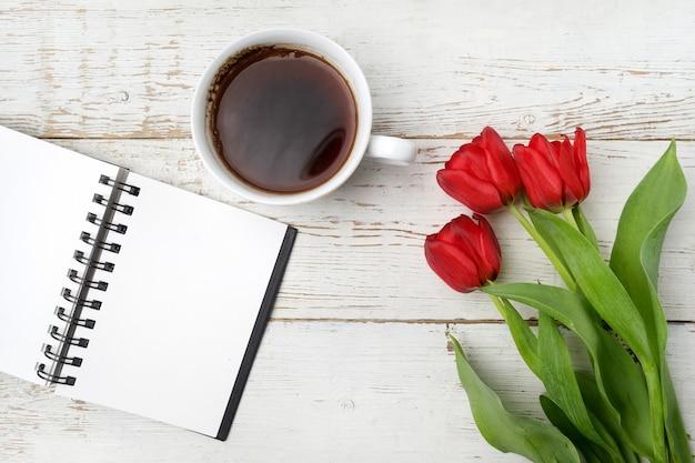 Tulipani rossi, tazza di caffè e taccuino sulla tavola di legno bianca